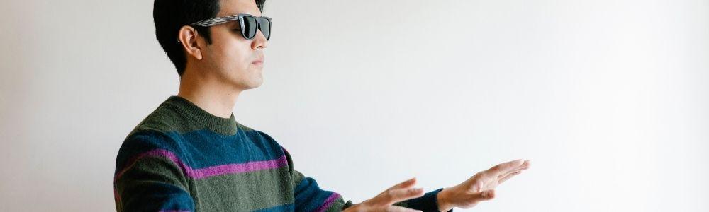 um homem com óculos escuros tateando